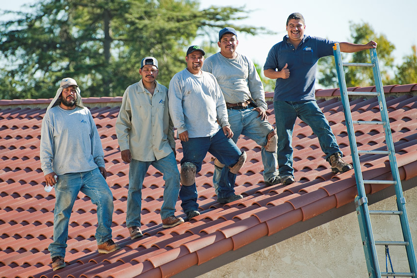Navarro Roofing crew standing on finished clay tile roof installed with foam.