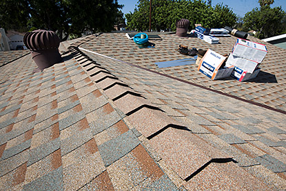 Ridge and roof under construction using high profile asphalt shingles